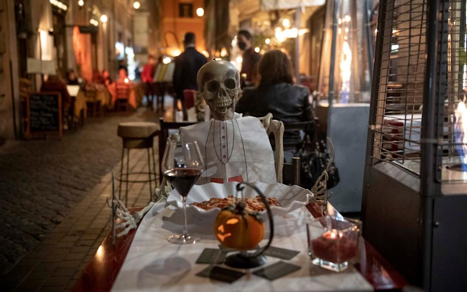 A skeleton is seen at a restaurant table to protest against the new national restriction to contain the coronavirus pandemic - Antonio Masiello/Getty