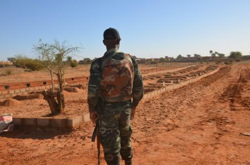 A Niger soldier looks at the graves of 71 Niger troops soldiers killed  in a jihadist attack on December 10, 2019, ahead of a regional summit to coordinate a response to the growing unrest