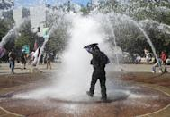 <p>A right-wing supporter of the Patriot Prayer group cools off in a fountain during a rally in Portland, Ore., Aug. 4, 2018. (Photo: Jim Urquhart/Reuters) </p>