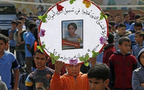 <span>Palestinian pupils hold a commemorative picture of their late classmate Moaz Abu Malhous at his school in Deir al-Balah town in central Gaza Strip, on November 16, 2019, two days after he was reportedly killed in an Israeli strike.</span> <span>Credit: AFP </span>