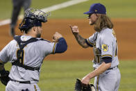 Milwaukee Brewers catcher Manny Pina, left, celebrates with relief pitcher Josh Hader, right, after a baseball game against the Miami Marlins, Saturday, May 8, 2021, in Miami. The Brewers won 6-2. (AP Photo/Lynne Sladky)