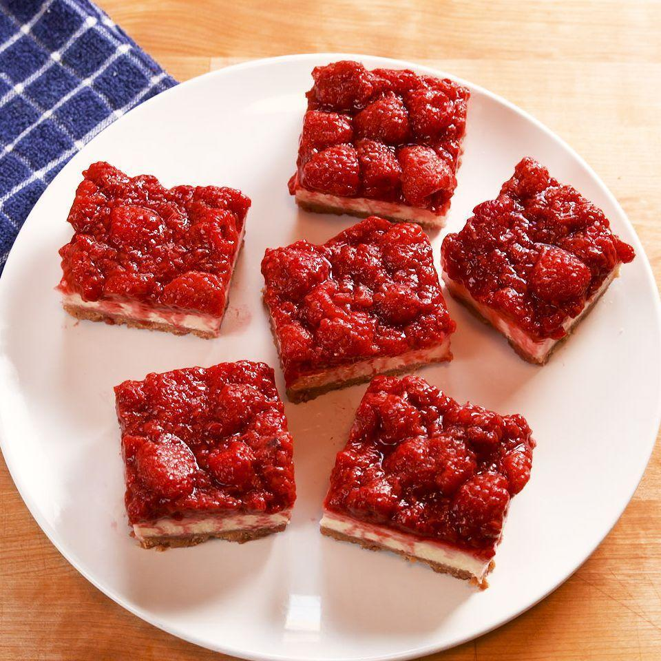 """<p>A sweet, creamy lemon cheesecake is topped with a tart raspberry jam for the perfect refreshing treat. Making cheesecake bars rather than a full cheesecake cuts down on bake time significantly and makes it stress free. We still recommend baking the cheesecake in a water bath to prevent the top from cracking! </p><p>Get the <a href=""""https://www.delish.com/uk/cooking/recipes/a33388684/raspberry-cheesecake-bars-recipe/"""" rel=""""nofollow noopener"""" target=""""_blank"""" data-ylk=""""slk:Raspberry Cheesecake Bars"""" class=""""link rapid-noclick-resp"""">Raspberry Cheesecake Bars</a> recipe.</p>"""