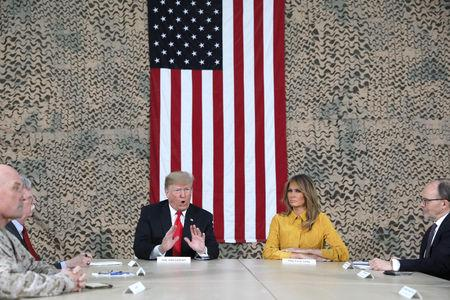 U.S. President Donald Trump, flanked by National Security Adviser John Bolton, first lady Melania Trump and U.S. Ambassador to Iraq Doug Silliman, meets political and military leaders during an unannounced visit to Al Asad Air Base, Iraq December 26, 2018. REUTERS/Jonathan Ernst
