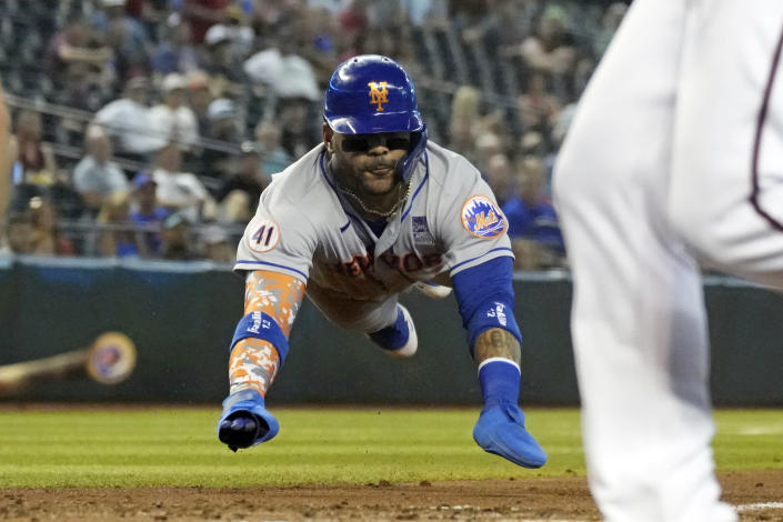 New York Mets' Jonathan Villar slides in head first to score a run against the Arizona Diamondbacks on a ball hit by James McCann in the second inning during a baseball game, Wednesday, June 2, 2021, in Phoenix. (AP Photo/Rick Scuteri)