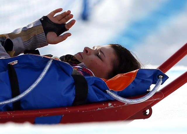 Jacqueline Hernandez of the United States is carried off the course in a stretcher after crashing in a seeding run during women's snowboard cross competition at the Rosa Khutor Extreme Park, at the 2014 Winter Olympics, Sunday, Feb. 16, 2014, in Krasnaya Polyana, Russia. (AP Photo/Sergei Grits)