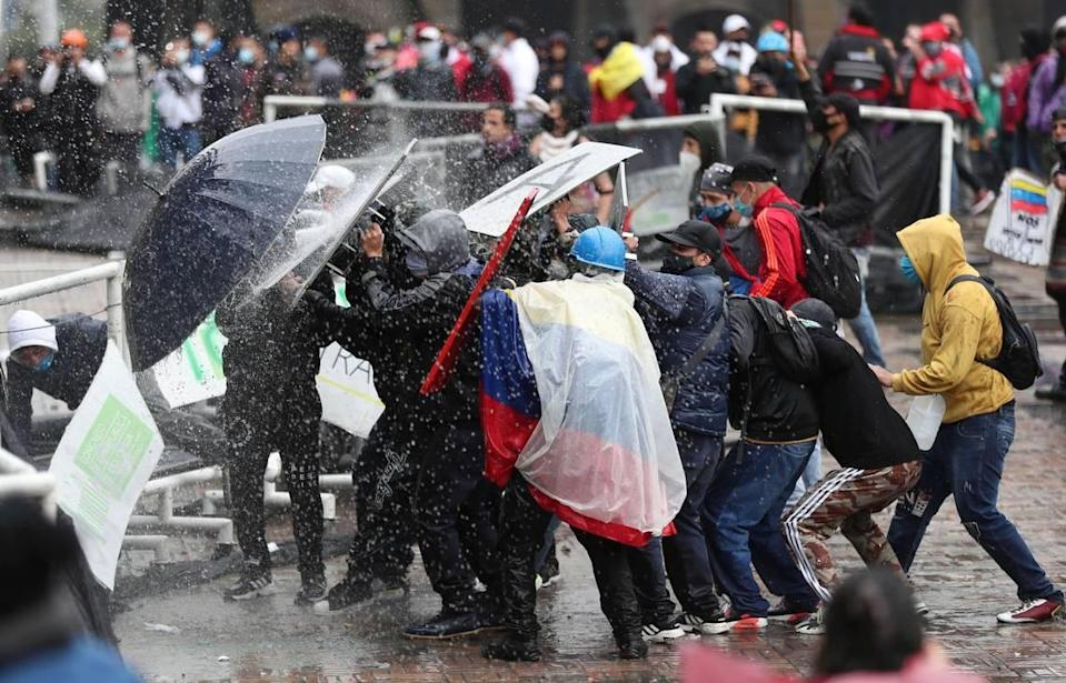 Anti-government protesters clash with police in Bogota, Colombia, Wednesday, May 5, 2021. The protests that began last week over a tax reform proposal continue despite President Ivan Duque's withdrawal of the tax plan on Sunday, May 2. (AP Photo/Fernando Vergara)
