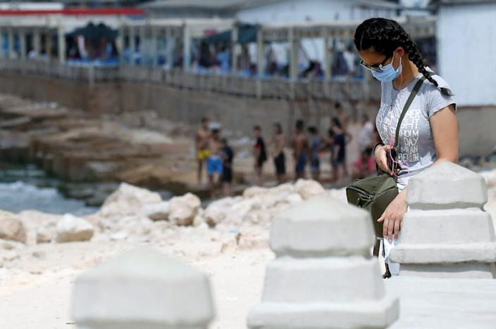 """A woman wearing a protective face mask walks along the Mediterranean Sea as the government closes beaches in Alexandria, Egypt, on August 7, 2020. <p class=""""copyright"""">REUTERS/Amr Abdallah Dalsh</p>"""