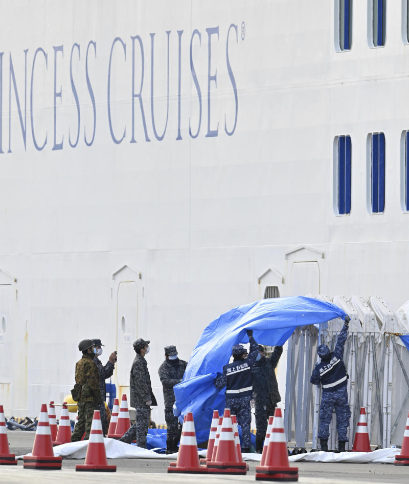 Japan Self Defense Force officials work as the ship receives food and supplies for passengers and crew members. Source: AAP