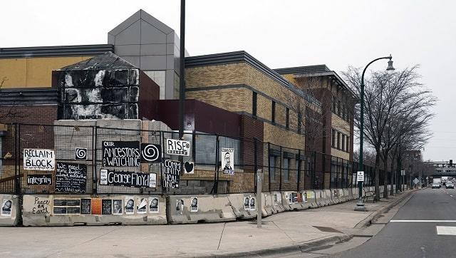 Signs hang on a fence amid the remains of the Minneapolis 3rd Precinct police station that was burned down by protesters. (AP Photo/Jim Mone)
