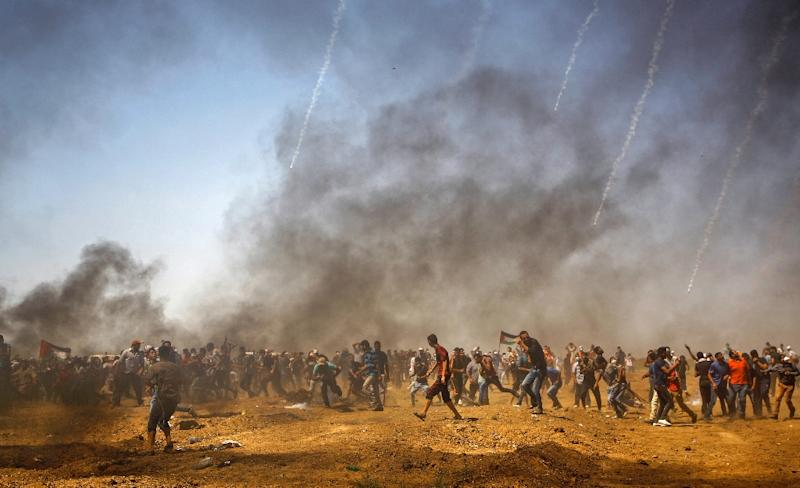 Palestinian protestors take cover from tear gas during a demonstration along Gaza's border with Israel on June 8, 2018 (AFP Photo/Mohammed ABED)