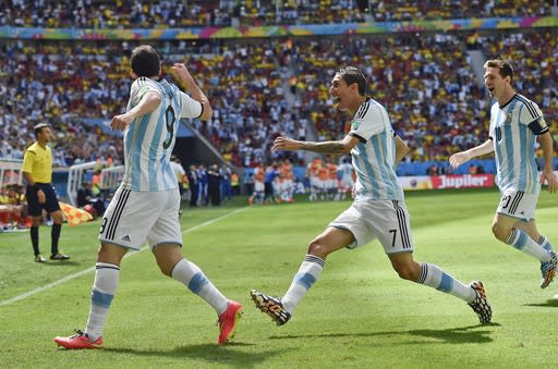 Argentina's Gonzalo Higuain, left, celebrates with Angel di Maria, center, and Lionel Messi after he scored the opening goal during the World Cup quarterfinal soccer match between Argentina and Belgium at the Estadio Nacional in Brasilia, Brazil, Saturday, July 5, 2014. (AP Photo/Martin Meissner)