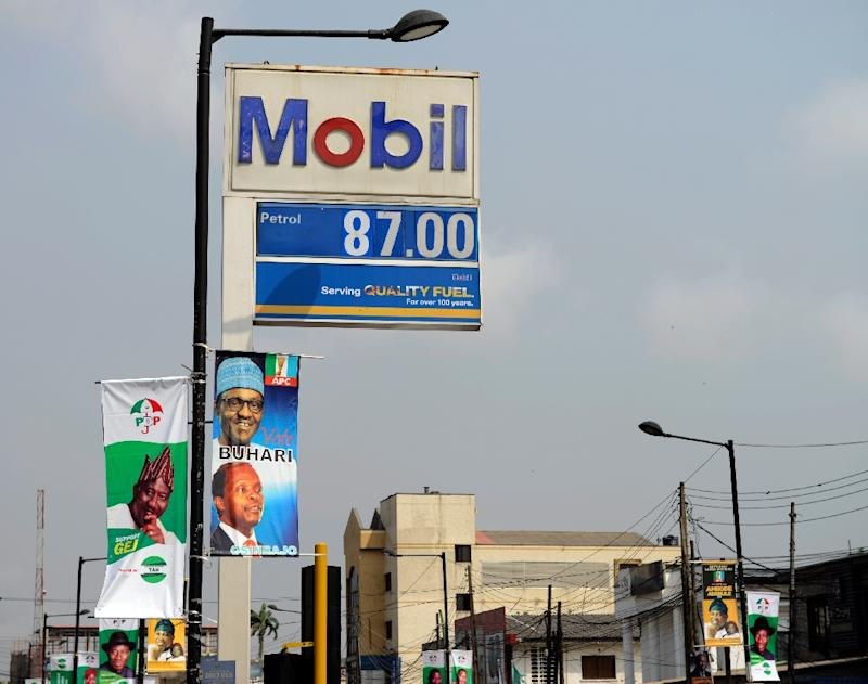 Presidential campaign posters hang from a lamppost in front of a petrol station in Lagos in the run-up to the vote