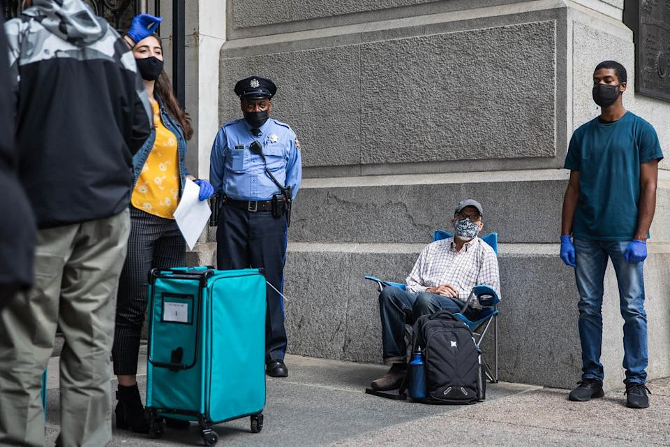 Man sits in folding chair near a line of voters and a police officer