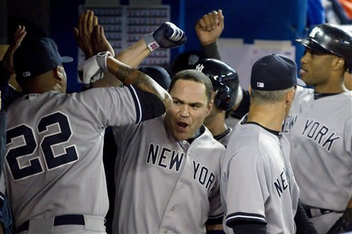 New York Yankees' Russell Martin celebrates with Andruw Jones, left, after hitting a three-run home run during the sixth inning of a baseball game against the Toronto Blue Jays in Toronto on Friday, Sept. 28, 2012. (AP Photo/The Canadian Press, Chris Young)