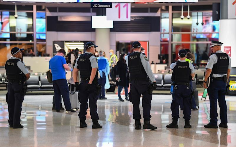 New South Wales police officers look on as passengers arrive from a Qantas flight that flew from Melbourne. The NSW-Victoria border will close at 11.59pm due to a surge in cases - Getty Images Asia