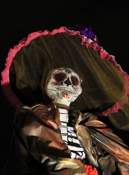 "A traditional Mexican ""Catrina"" sits at Mexico's National Autonomous University during Day of the Dead celebrations in Mexico City, Wednesday, Oct. 30, 2013. Known as the ""Catrina,"" the figure of a skeleton wearing an elegant broad-brimmed hat was first done as a satirical engraving by artist Jose Guadalupe Posada somewhere between 1910 and his death on Jan. 20, 1913. (AP Photo/Marco Ugarte)"