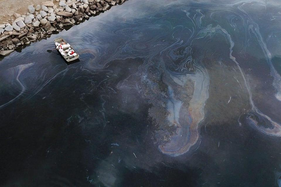 This aerial picture taken on October 4, 2021 shows environmental response crews cleaning up oil that flowed near the Talbert marsh and Santa Ana River mouth, creating a sheen on the water after an oil spill in the Pacific Ocean in Huntington Beach, California. (AFP via Getty Images)