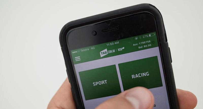 A person uses the TAB app on their iPhone. Batting apps can be used to bet on The Melbourne Cup. Source: AAP.
