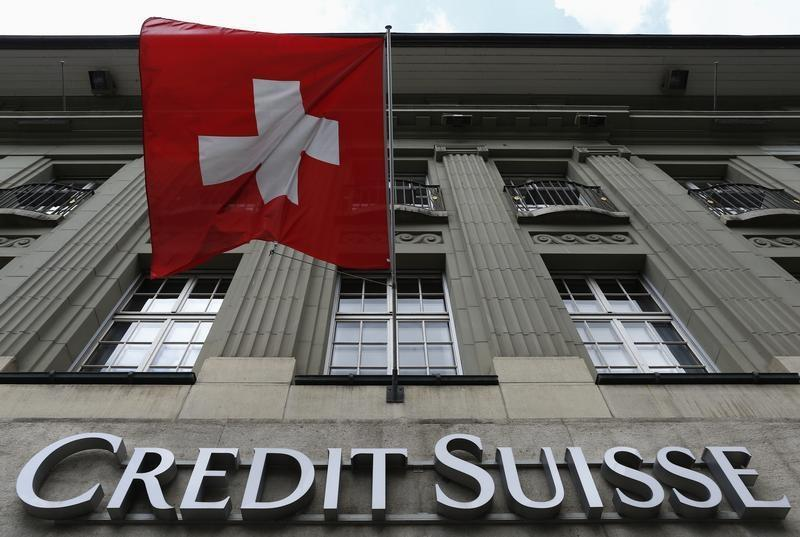The logo of Swiss bank Credit Suisse is seen below the Swiss flag at a building in the Federal Square in Bern