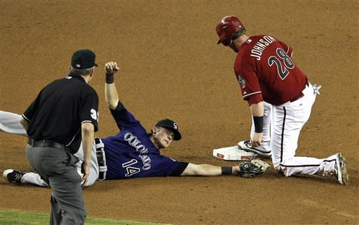 Colorado Rockies' Josh Rutledge (14) dives but is unable to get a tag on Arizona Diamondbacks' Chris Johnson (28) as Johnson steals second base and umpire Gary Darling looks on during the second inning of a baseball game on Wednesday, Oct. 3, 2012, in Phoenix. (AP Photo/Ross D. Franklin)