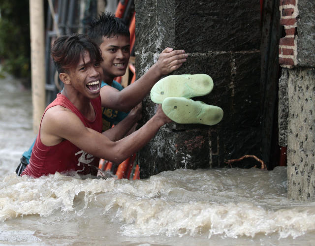 FILE - In this Aug. 19, 2013 file photo, Filipino men struggle to cross strong currents as floodwaters rise at a residential area in Las Pinas, south of Manila, Philippines. Lashed each year by typhoons and stuck with outdated drainage systems, the Philippine capital has been hit by ever-worsening floods. Population growth, inadequate infrastructure, corruption, deforestation and even trash build-up combine to exacerbate the impact. It's a trend experts expect to continue. (AP Photo/Aaron Favila, File)