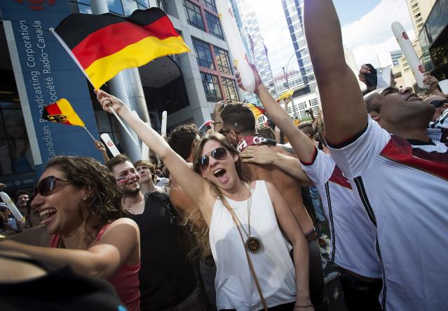 German supporters celebrate following Germany's 1-0 victory over Argentina in the World Cup soccer final in Brazil, on Front Street in Toronto on Sunday, July 13, 2014. AP Photo/The Canadian Press, Darren Calabrese)