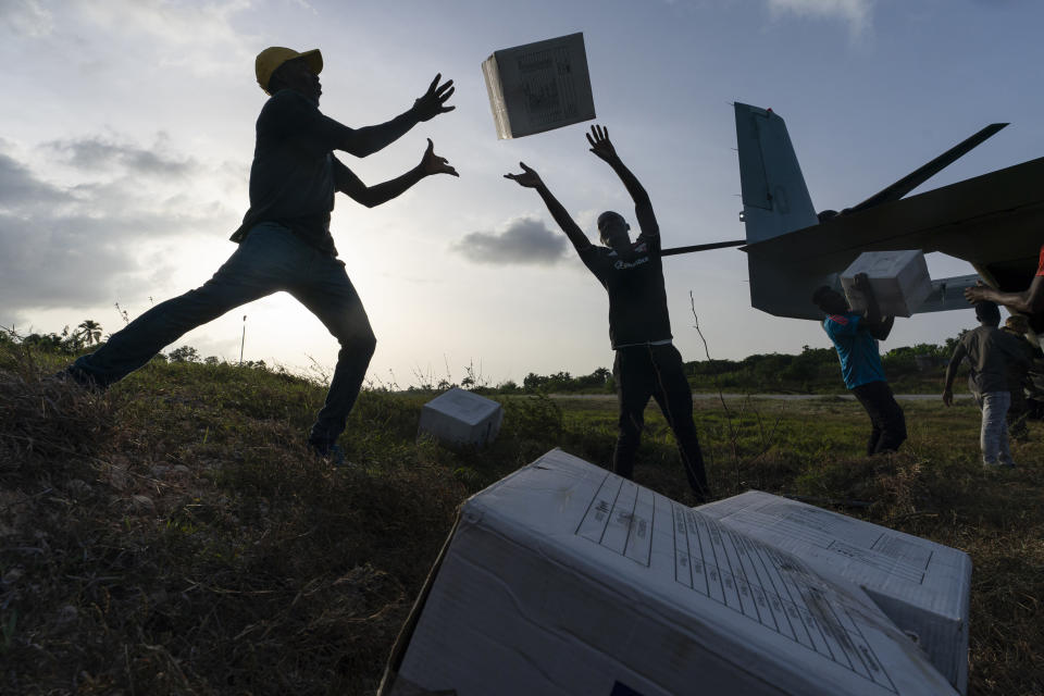 """Haitian aid workers unload food from a VM-22 Osprey at Jeremie Airport, Saturday, Aug. 28, 2021, in Jeremie, Haiti. The VMM-266, """"Fighting Griffins,"""" from Marine Corps Air Station New River, from Jacksonville, N.C., are flying in support of Joint Task Force Haiti after a 7.2 magnitude earthquake on Aug. 22, caused heavy damage to the country. (AP Photo/Alex Brandon)"""