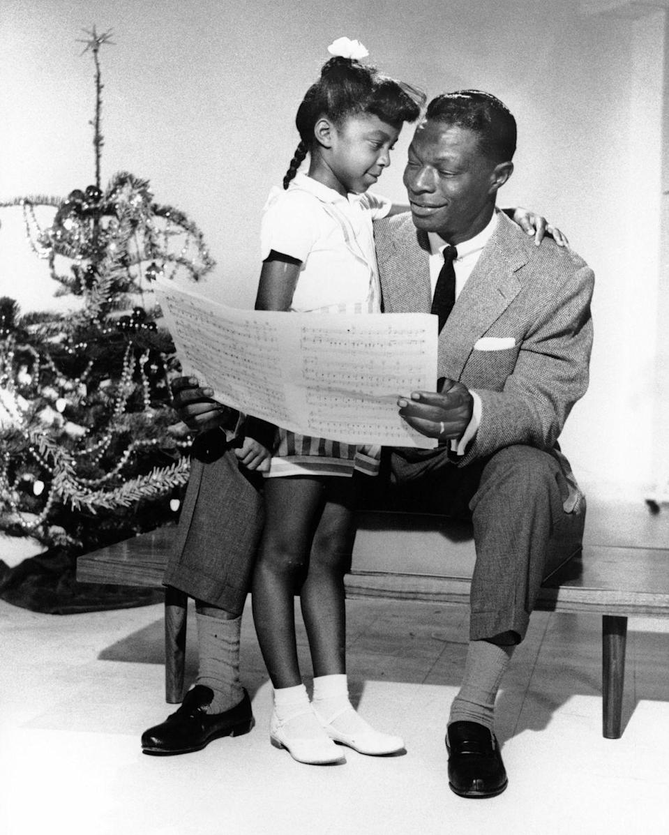 <p>Nat King Cole accessorized his simple grey suit with a white pocket square and a black skinny tie during a 1960 holiday photoshoot with his daughter, Natalie. </p>