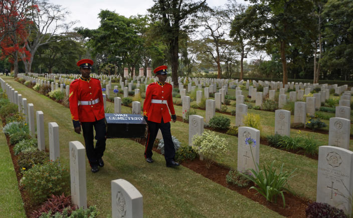 """FILE - In this Sunday, Nov. 13, 2016 file photo, two members of Kenya's Military Police walk past graves as they leave after attending a Remembrance Sunday event, to honor the contribution of those British and Commonwealth military who died in the two World Wars and later conflicts, at the Nairobi War Cemetery in Kenya. The Commonwealth War Graves Commission has apologized after an investigation found that at least 161,000 mostly Africans and Indians who died fighting for the British Empire during World War I weren't properly honored due to """"pervasive racism"""", according to findings released Thursday, April 22, 2021. (AP Photo/Ben Curtis, File)"""