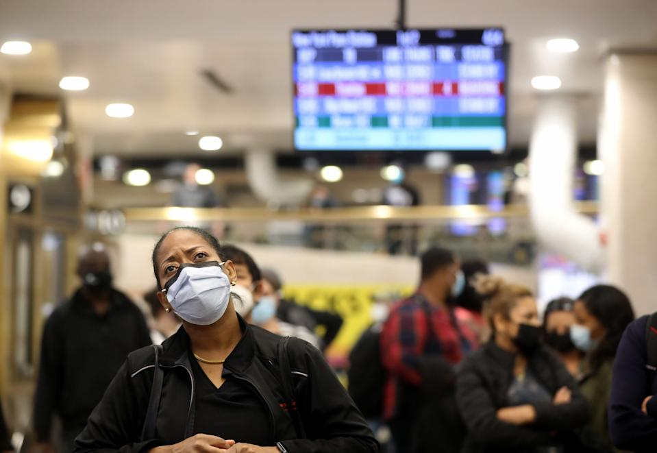 Commuters wait to see what track their homebound NJ Transit train will be leaving from during rush hour at Penn Station Nov. 9, 2020. The COVID-19 pandemic has caused the number of commuters to decrease to a fraction of those who used the terminal prior to the pandemic.