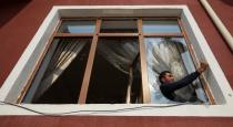 A man removes glass from a window that was allegedly damaged by recent shelling during the fighting over the breakaway region of Nagorno-Karabakh, in the city of Tartar