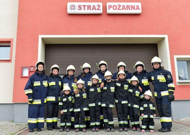 PHOTO: Girls pose with the volunteer fire department in the town of Miejsce Odrzanskie, Poland, July 31, 2019. (Lukasz Kalinowski/East News via Polaris)
