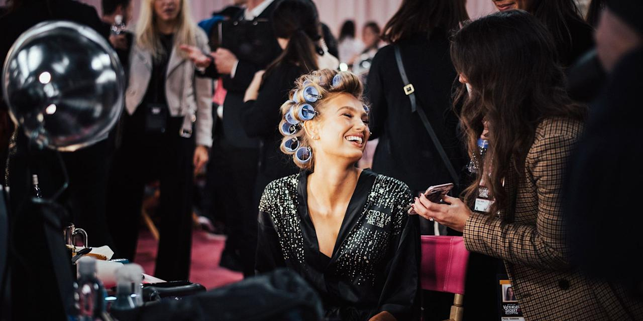 <p>Romee Strijd laughs while getting her hair done and giving interviews backstage. </p>