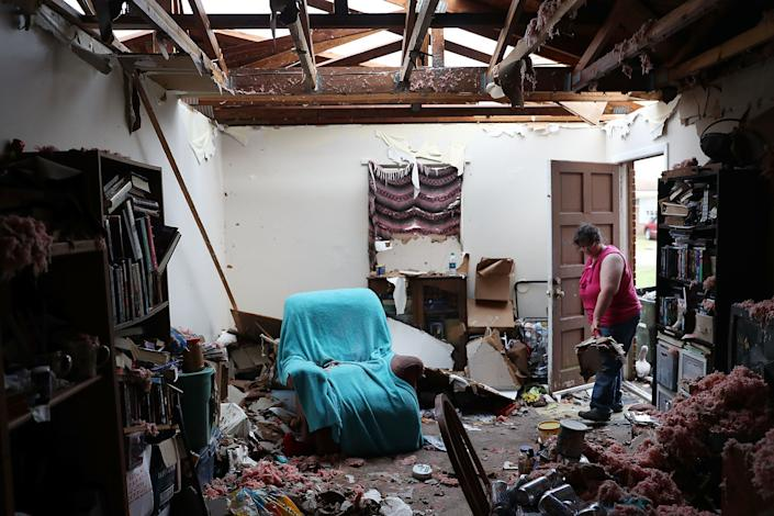 Amanda Logsdon begins the process of trying to clean up her home in Panama City after the roof was blown off.