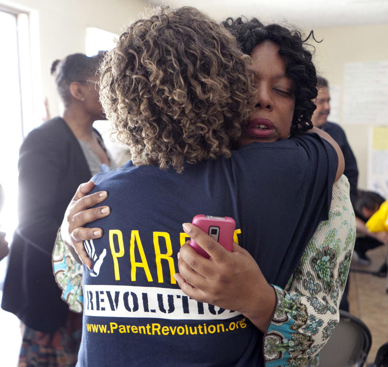 In this Tuesday, Sept. 13, 2011,  photo, Parent Revolution member, Casondra Perry, right, cries as she gets a hug after a meeting to discuss how they are pushing change at their Woodcrest Elementary School in Los Angeles.  In California, school parent groups are no longer just about holding the next bake-sale fundraiser, they have also began to push for education reform. (AP Photo/Damian Dovarganes)