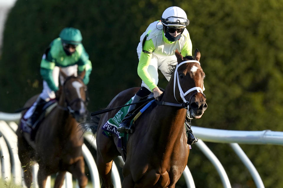 Jockey Florent Geroux eases up Aunt Pearl after they won the Breeders' Cup Juvenile Fillies Turf horse race at Keeneland Race Course, Friday, Nov. 6, 2020, in Lexington, Ky. (AP Photo/Mark Humphrey)