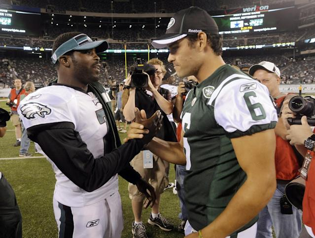 FILE - In this Sept. 1, 2011, file photo, Philadelphia Eagles' Michael Vick, left, greets New York Jets' Mark Sanchez after a preseason NFL football game in East Rutherford, N.J. The Jets signed Vick and released Sanchez on Friday, March 21, 2014. Vick was a free agent after spending the last five seasons with the Phialdelphia Eagles. (AP Photo/Bill Kostroun, File)