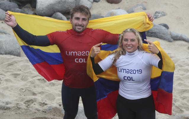 Giorgio Gomez and his sister Isabella Gomez, of Colombia, pose for photos after the pair both won a gold medal for paddle, in the women's and men's SUP surfing events, during the Pan American Games on Punta Rocas beach in Lima Peru, Sunday, Aug. 4, 2019. (AP Photo/Martin Mejia)