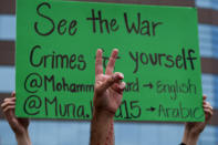 A demonstrator shows a peace sign during a protest outside the Federal Building against Israel and in support of Palestinians, Saturday, May 15, 2021 in the Westwood section of Los Angeles. (AP Photo/Ringo H.W. Chiu)