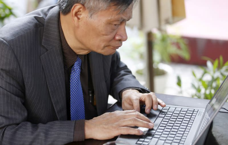 FILE PHOTO: Nguyen Quang A writes a comment on Facebook while sitting at a cafe after an interview in Hanoi