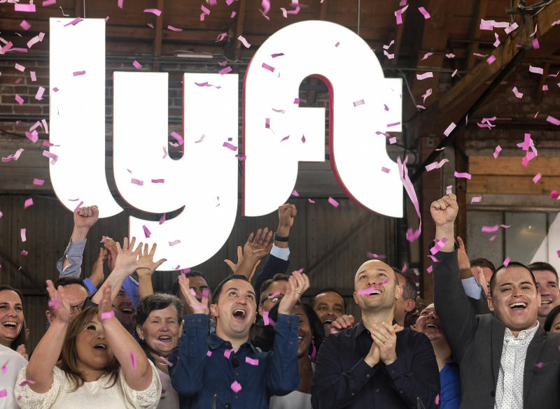 "Lyft co-founders John Zimmer, front second from left, and Logan Green, front second from right, cheer as they as they ring a ceremonial opening bell in Los Angeles, Friday, March 29, 2019. On Friday the San Francisco company's stock will begin trading on the Nasdaq exchange under the ticker symbol ""LYFT."" (AP Photo/Ringo H.W. Chiu)"