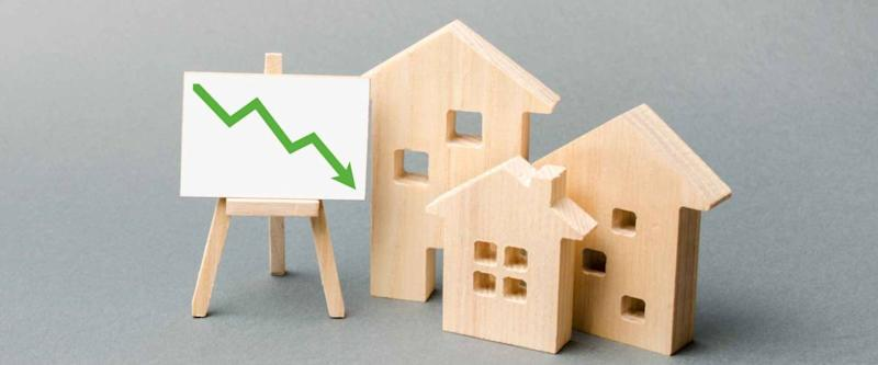 Wooden houses and an easel arrow down represent falling mortgage rates.