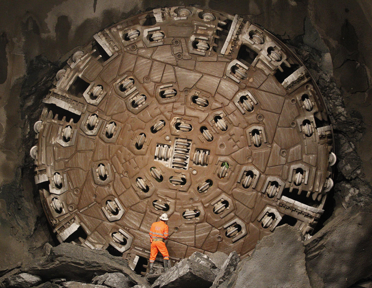 A miner stands in front of the drill machine 'Sissi' after it broke through the rock at the final section Faido-Sedrun, at the construction site of the NEAT Gotthard Base Tunnel October 15, 2010. With a length of 57 km (35 miles) crossing the Alps, the world's longest train tunnel should become operational at the end of 2017.            REUTERS/Christian Hartmann (SWITZERLAND  - Tags: TRANSPORT BUSINESS BUSINESS CONSTRUCTION POLITICS IMAGE OF THE DAY TOP PICTURE) FOR BEST QUALITY IMAGE SEE: GM1E6CG0XUC01 - RTXTGU6