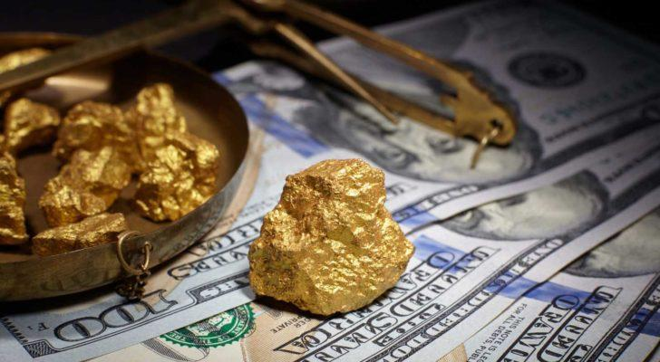 Gold nuggets on top of American paper money representing gold stocks