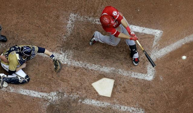 Los Angeles Angels' Mike Trout. right, hits a single during the sixth inning of a baseball game against the Milwaukee Brewers, Sunday, Sept. 1, 2013, in Milwaukee. (AP Photo/Morry Gash)