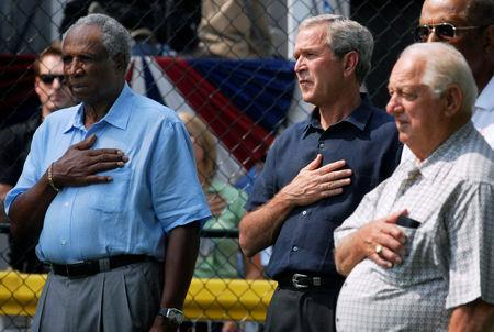 FILE PHOTO: U.S. President George W. Bush (C) stands for the National Anthem with baseball Hall of Famers Frank Robinson (L) and Tommy Lasorda before a tee ball game on the South Lawn of the White House in Washington July 15, 2007. REUTERS/Jonathan Ernst/File Photo