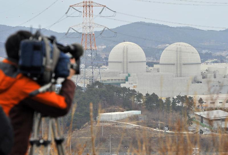 A cameraman takes video footage on February 5, 2013 of the Shin-Kori 3 and 4 under construction in Gori near South Korea's southern port of Busan