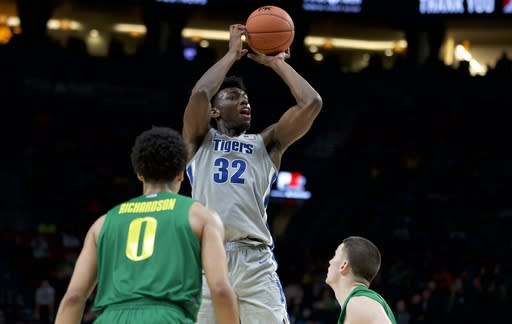 FILE - In this Nov. 12, 2019, file photo, Memphis center James Wiseman, center, shoots in front of Oregon guards Will Richardson, left, and Payton Pritchard during the second half of an NCAA college basketball game in Portland, Ore. The Golden State Warriors selected Wiseman in the NBA draft Wednesday, Nov. 18, 2020. (AP Photo/Craig Mitchelldyer, File)