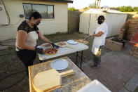 Ruby Salgado, left, and her husband chef Jose Hernandez prepare pizzas in the backyard of their home in Scottsdale, Ariz. on April 3, 2021. Beaten down by the pandemic, some laid-off or idle restaurant workers have pivoted to dishing out food from home. (AP Photo/Ross D. Franklin)