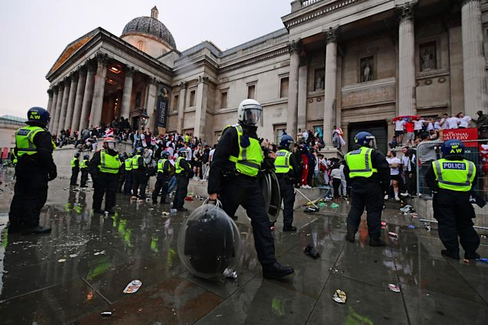 A police officer carries riot shields as colleagues observe England fans on the steps of the National Gallery, in Trafalgar Square, London during the UEFA Euro 2020 Final between Italy and England. Picture date: Sunday July 11, 2021.